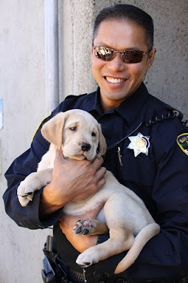 San Rafael Police Officer Ed Chiu holding a yellow Lab puppy.