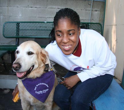 A young girl gives an ambassador dog a hug