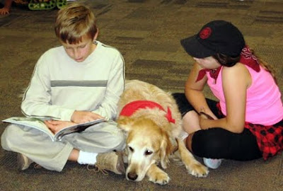 Two children reading to a Golden Retriever