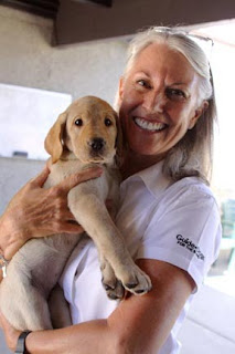 Puppy raiser Kim Hart holding a yellow Lab pup