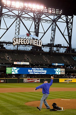 Bob Sonnenberg throws out the first pitch at a Mariners-Angels baseball game; his guide Nino is by his side.