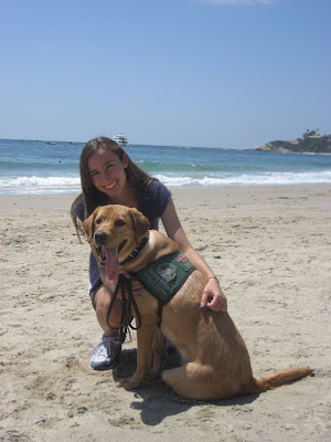 Elizabeth and yellow Lab puppy on the beach