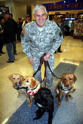 Army Chief of Staff General Casey crouches down to be photographed with four of Lone Star Puppy Raising Club's Guide Dog puppies-in-training. The puppies sport red, white and blue scarves for the occasion.