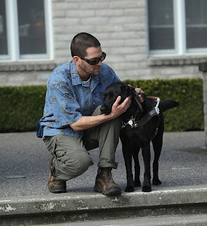 GDB graduate Seth Webster hugs his black Lab Guide Dog Bamboo