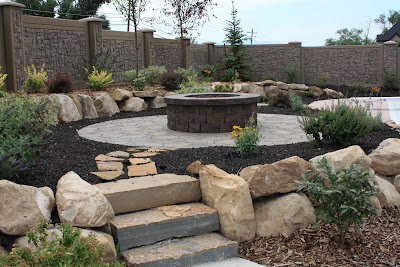 Rock steps lead up from the sidewalk to a flagstone path and onto the fire  pit. - Landscaping Utah, Wasatch, Summit, & Salt Lake CountiesKuhni