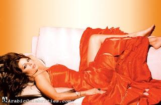 haifa wahbi etendu sur un lit en robe rouge