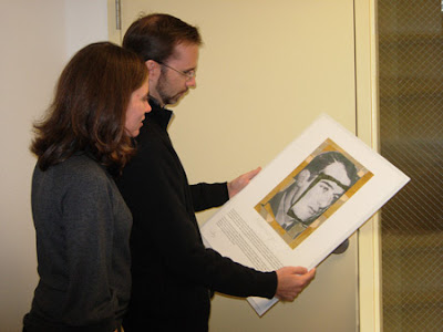 Adrienne Hutelmyer and Paul Berg, Executive Director, examine a portrait of Raoul Wallenberg