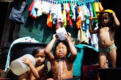 Children take a bath to cool off from the summer heat at a slum area in Tondo, Metro Manila