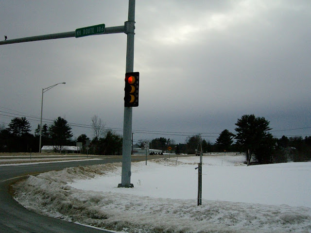 Stop light at a snow-covered intersection in New Hampshire.