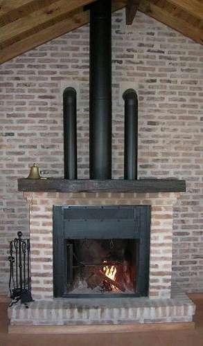Chimenea de ladrillos y metal con tubos para distribuir calor