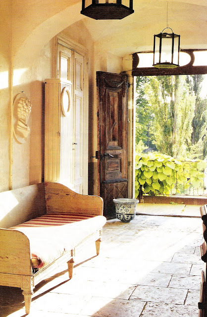 Inviting entrance with wooden door, stone floors, bench with and upholstered cushion, House Beautiful Magazine, edited by lb for linenandlavender.net
