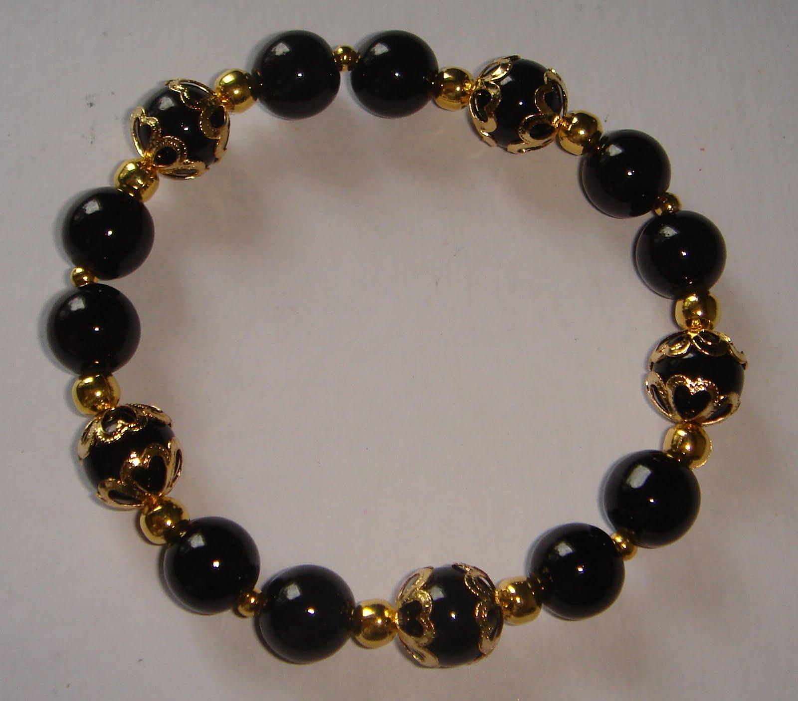 104 B 70 Collar de piedras negras con detalle en corazón dorado. Pulsera y aros.