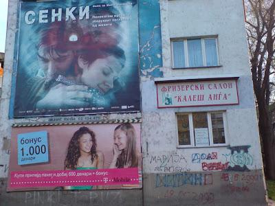 Зграда во центарот на Скопје со реклами и една парола поставена на прозорец.