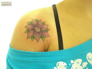 Flor roxa tatuada no ombro.