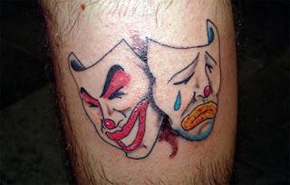 Máscaras de teatro tatuadas na perna