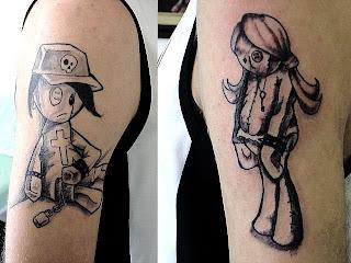 Boneco e boneca de pano tatuados no braço