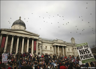 Green Party Keep the NHS Public placard above crowds in Trafalgar Square