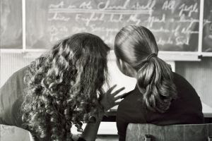 Alunas cochichando em sala de aula