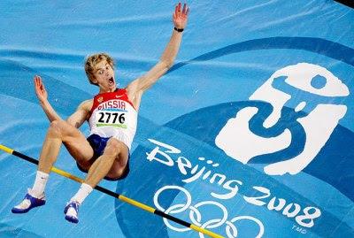 Saltador russo pula sobre a barra, com logotipo das olimpíadas ao fundo