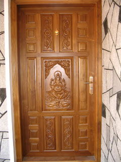 Picture shows front door in teak wood of Edappally house with carving
