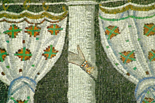 Mosaic of hand symbol on pillar, with curtains on both sides.
