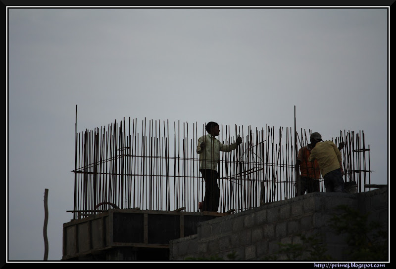 Workers constructing a water tank on top of a building