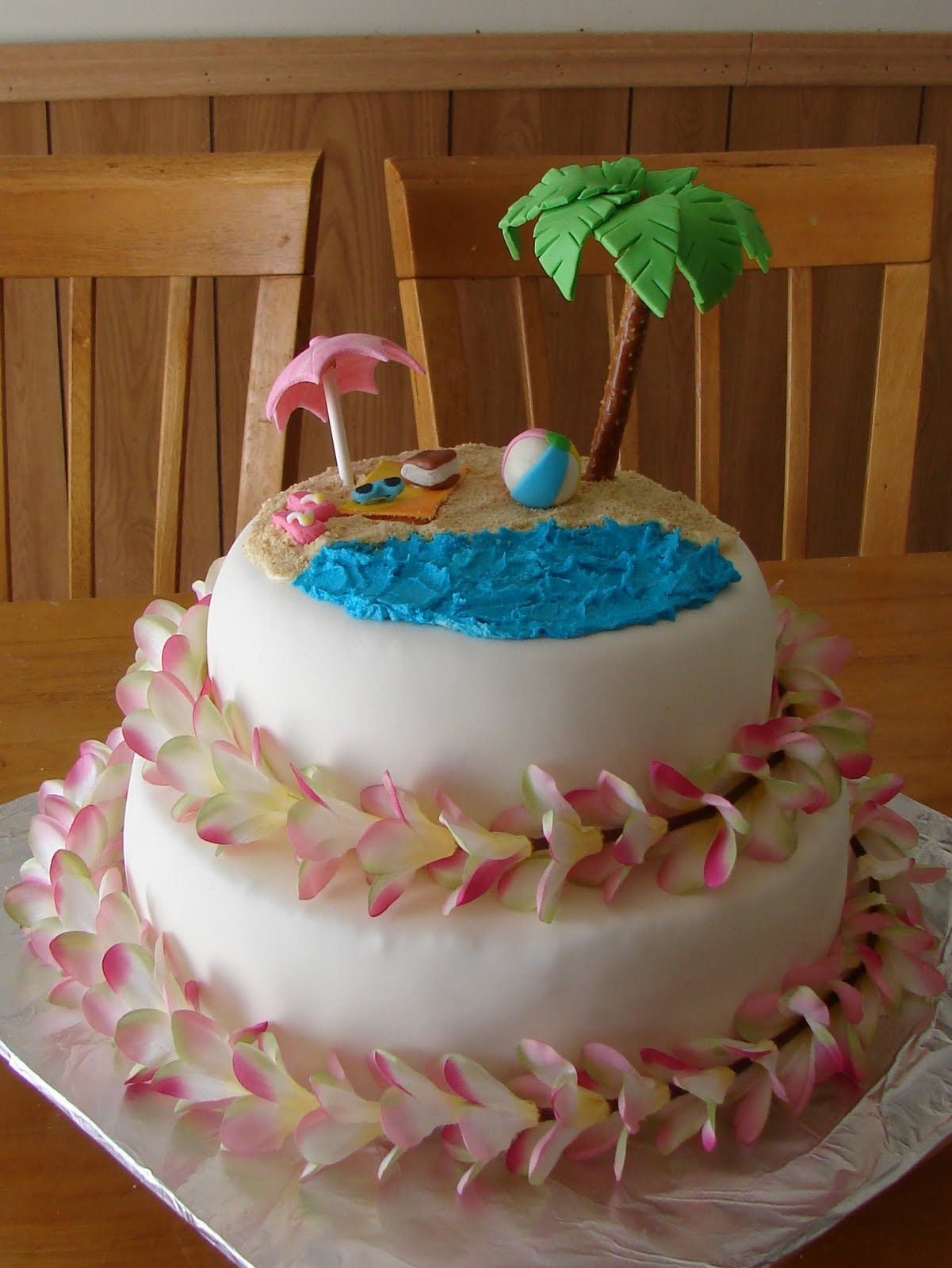 this cake was done for a hawaiian themed bridal shower the umbrella and tree were so fun to make all of the decorations on the top are shaped with mm