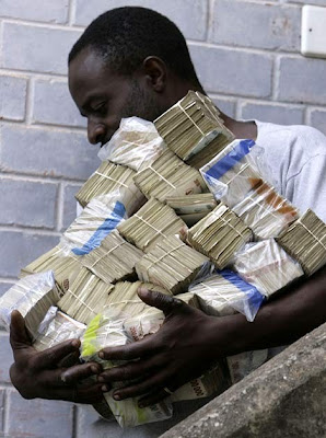 Man carries a mountain of Zimbabwe currency worth about $100 US