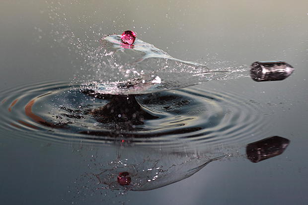 A bullet is captured as it slices through a water splash