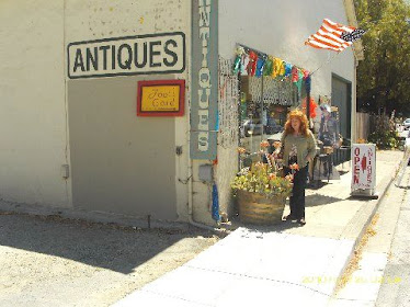 Unknown woman in front of antique shop...