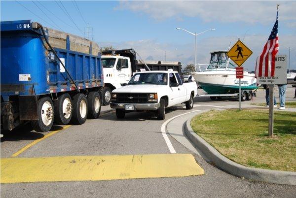 Pedestrian crossing, dump trucks & boats on trailers.