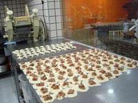 fechamento das esfihas em mesa de produção