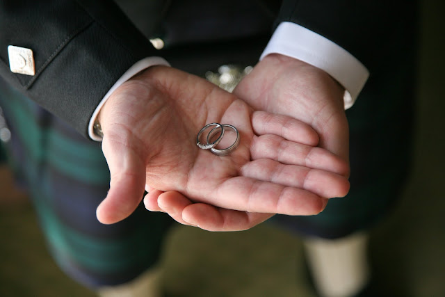 Groom holds wedding rings in his hands