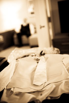 Groom's tuxedo laid out on bed in Courtyard Marriott