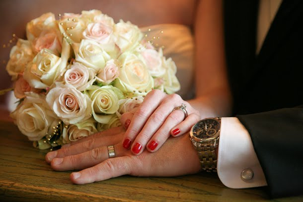 Bride and groom hold hands so you can see wedding rings with bouquet in background