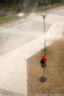 bättre liten skugga, än ingen alls, lyktstolpe, skuggar man i röd tröja, solig dag