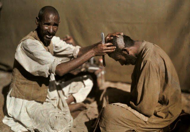 An Afridi barber shaves a fellow tribesmen's hair - Khyber Pass 1929