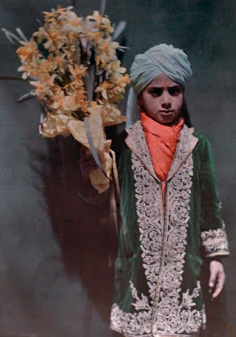 A boy awaits the arrival of the Viceroy and Lady Irwin with flowers - Srinagar 1929