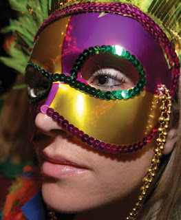 A beautiful and sexy girl wearing Gold color Mardi gras festival mask with mardi gras breeds looks cute on her face gallery