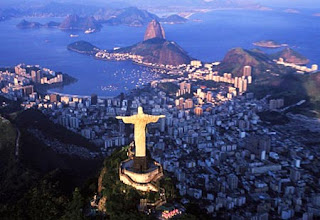 Backside aerial night evening view of Christ the redeemer statue in lighting near the bay