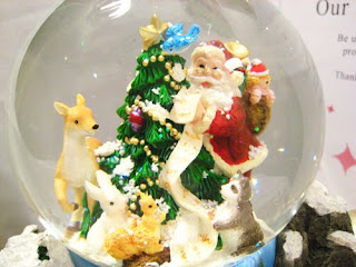 Santa Claus with gifts and rabbits at Christmas Tree in the Transparent Christmas snow globe