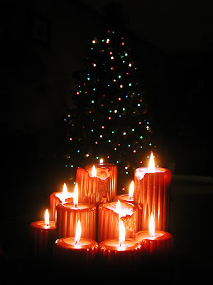 Bright glow of reddish yellow Christmas candles at Christmas tree photo free Christian Christmas image download