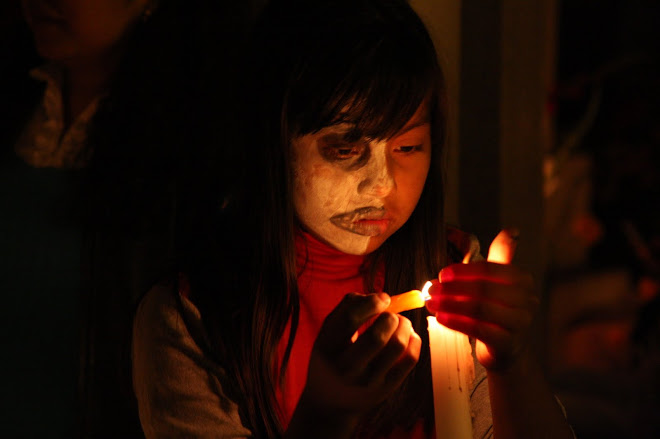 Young girl lighting candles at gravesite