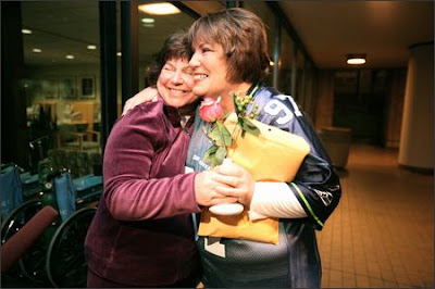 Annamarie Ausnes, left, greets barista Sandie Andersen with a rose on Andersen's arrival at Virginia Mason Medical Center for the kidney transplant surgery Tuesday. All went fine.