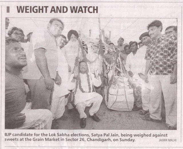 BJP candidate for the Lok Sabha elections, Satya Pal Jain, being weighed against sweets at the grain market .........
