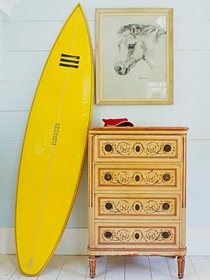 yellow surfboard next to chest