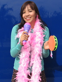 Photo of a cute teenager with a microphone and dressed in pink boa