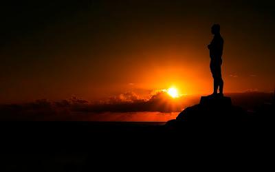 homem meditando no pôr do sol, alto da montanha