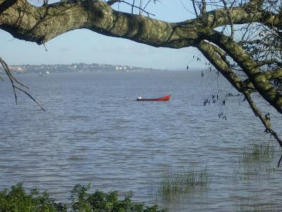 foto de pescador em um barco vermelho atravessando o rio Guaíba em Porto Alegre