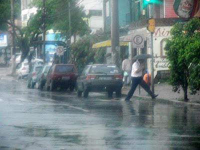 pedestre pulando uma poça d'água na chuva em porto alegre